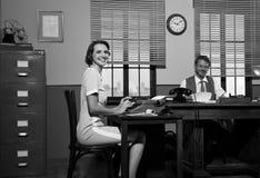 Smiling director and secretary at work. Smiling director and secretary working in the office and smiling at camera Stock Photos