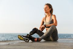 Smiling disabled athlete woman with prosthetic leg. Looking away while sitting at the beach stock photography