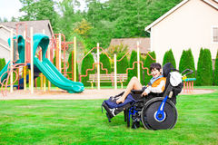 Smiling disabled boy in wheelchair sitting at a park Royalty Free Stock Photo