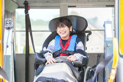 Smiling disabled boy in wheelchair on yellow school bus lift Royalty Free Stock Photos