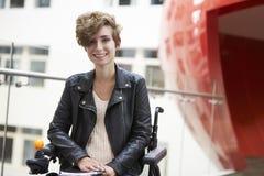 Smiling disabled female university student on mezzanine Stock Photo