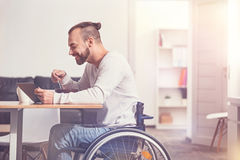 Smiling disabled male person eating soup. Tasty dinner. Positive delighted bearded man using tablet while watching film sitting in semi position at the table Royalty Free Stock Photography
