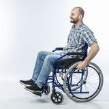 Smiling disabled man sitting in a wheelchair. Positive expression and casual clothes royalty free stock photography
