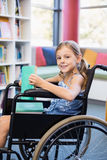 Smiling disabled school girl on wheelchair holding a books in library Stock Photography