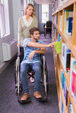 Smiling disabled student with classmate in library Royalty Free Stock Images