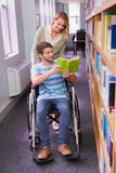 Smiling disabled student with classmate in library Stock Image