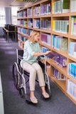 Smiling disabled student in library picking book Stock Image
