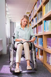 Smiling disabled student in library picking book Stock Images
