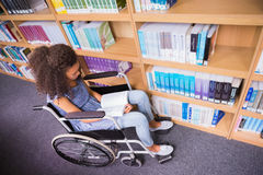 Smiling disabled student in library reading book Stock Photography