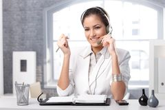 Smiling dispatcher with headset. Smiling dispatcher working at office desk with headset, holding microphone Stock Photo