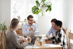 Smiling diverse colleagues brainstorming at casual office meetin. Diverse colleagues sit at wooden table laugh discussing company financial report at casual stock images