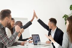 Smiling colleagues giving high five excited by business results. Smiling diverse colleagues giving high five at company meeting excited by shared goal stock photo