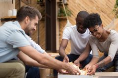 Smiling diverse multiethnic friends taking pizza slices from box. Smiling diverse multiethnic young friends taking pizza slices from box, eating Italian junk stock image