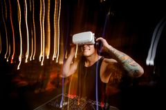 Smiling DJ in virtual reality glasses plays the track in club Stock Images