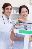 Smiling doctor adjusting scale for his patient Royalty Free Stock Image