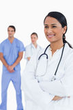 Smiling doctor with arms folded and colleagues behind her Royalty Free Stock Photos