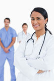 Smiling doctor with arms folded and staff Royalty Free Stock Images