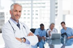 Smiling doctor with arms folded. Standing in front of his team Stock Image
