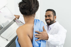 Smiling Doctor Assisting Patient Undergoing Mammogram X-ray Test Royalty Free Stock Images