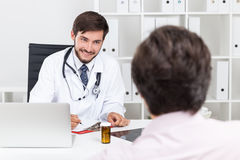 Smiling doctor with beard talking to his patient Stock Photos