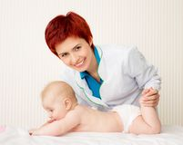 Smiling doctor with small baby Stock Photography