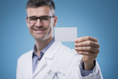 Smiling doctor with business card Royalty Free Stock Photo