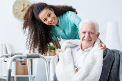 Smiling doctor caring about patient. At home stock image