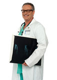 Smiling doctor carrying x-ray report of hand bone Stock Photography