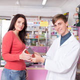 Smiling doctor and client inside pharmacy with product in hands Stock Photos