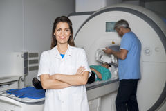 Smiling Doctor With Colleague Preparing Patient For CT Scan stock image