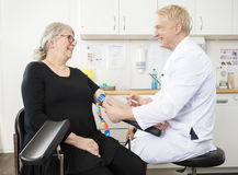 Smiling Doctor Collecting Senior Patient's Blood For Test In Cli. Smiling mature male doctor collecting senior patient's blood for test in clinic stock photography