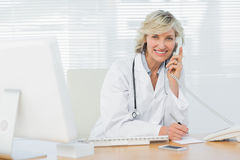 Smiling doctor with computer using phone at medical office Royalty Free Stock Images