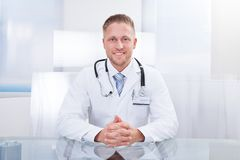 Smiling doctor or consultant sitting at a desk. With his stethoscope around his neck looking at the camera Royalty Free Stock Images