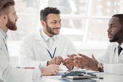 Smiling doctor discussing with affiliates during meeting Stock Photo