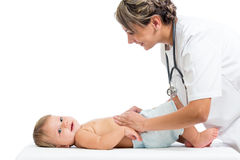 Smiling doctor examining baby stomach Royalty Free Stock Image