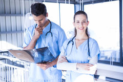 Smiling doctor examining a x ray report with his colleague. In hospital Royalty Free Stock Images