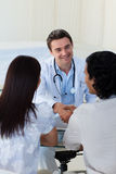 Smiling Doctor Explaining Diagnosis To A Couple Royalty Free Stock Photos