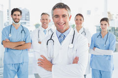 Smiling doctor with fellow doctors Stock Photography