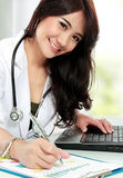 Smiling doctor female working in her office Stock Photos