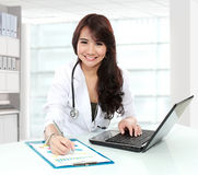 Smiling doctor female working in her office Stock Photo