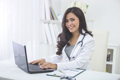 Smiling doctor female working in her office Stock Photography