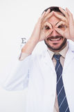 Smiling doctor forming eyeglasses with his hands Stock Image