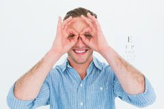 Smiling doctor forming eyeglasses with his hands Stock Photography