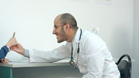 Smiling doctor giving little patient a lollipop after the exam. Smiling doctor giving little patinet a lollipop after the exam. Professional shot on BMCC RAW Royalty Free Stock Photos