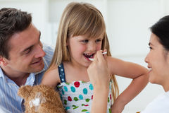 Smiling doctor giving medicine to a child. Accompanied by her father Royalty Free Stock Images