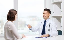 Smiling doctor giving pills to woman at hospital Stock Photo