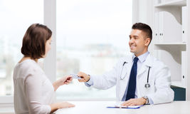 Smiling doctor giving pills to woman at hospital Royalty Free Stock Photos