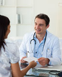 Smiling doctor giving a prescription Stock Images