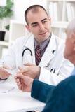 Smiling doctor giving a prescription Royalty Free Stock Photos