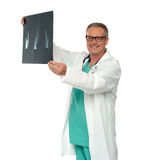 Smiling doctor in glasses reviewing x-ray report Royalty Free Stock Image